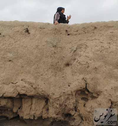 زنی در بالای دیوار سست قلعه روستای عاشقان